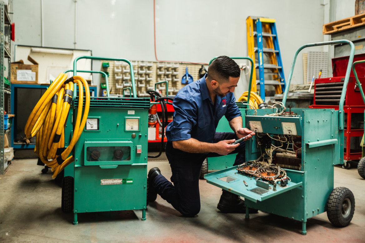 Worker performing maintenance on electrical equipment in a workshop