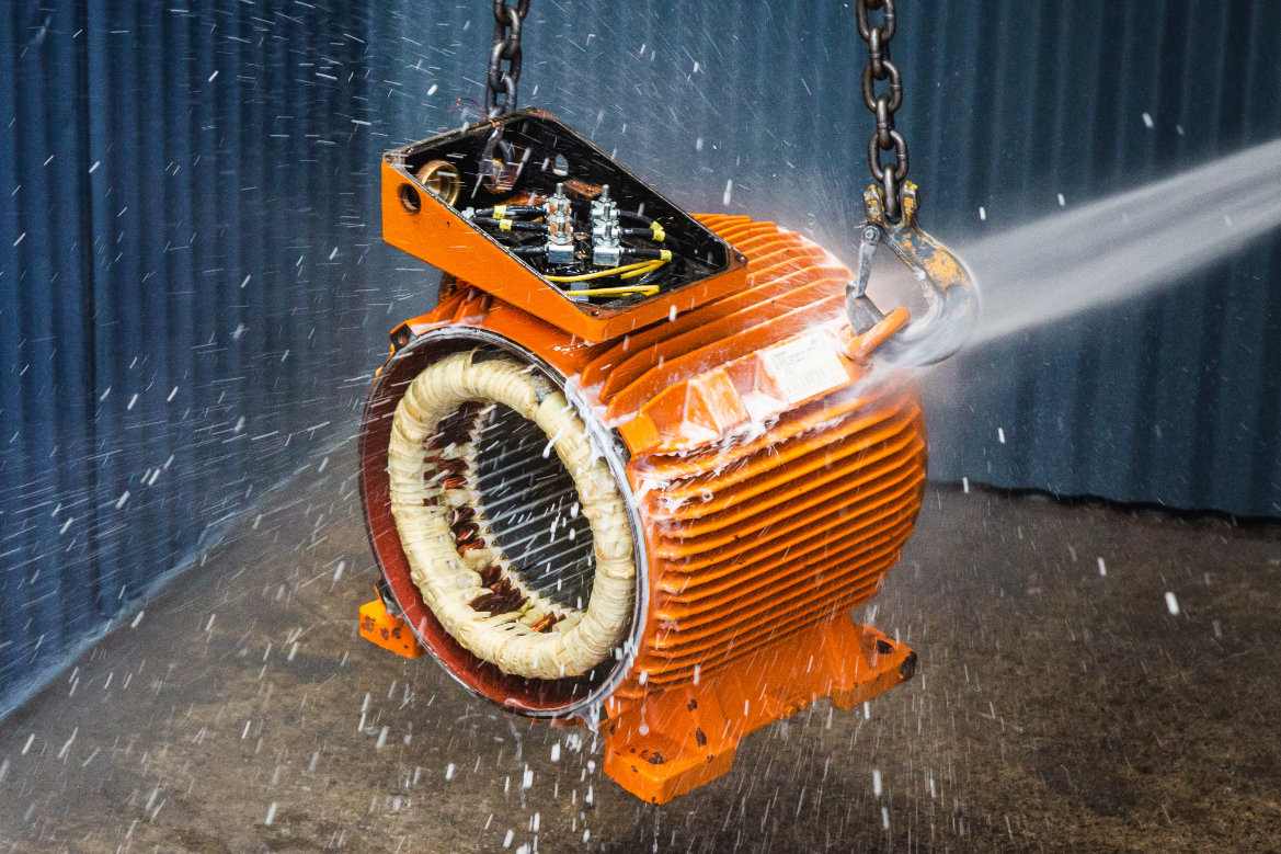 Electric motor being washed by pressure hose